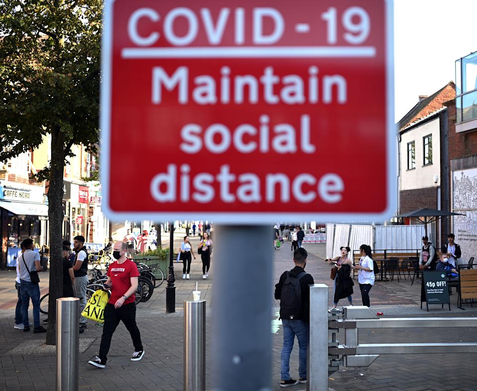 People walk past a sign encouraging social distance in a shopping street in Solihull, central England on September 14, 2020 after the British government imposed fresh restrictions on the area after a rise in cases of the novel coronavirus. - Authorities in Britain's second city of Birmingham announced new coronavirus restrictions Friday as the nation's viral reproduction rate, or R number, exceeded 1.0 for the first time since March. (Photo by Oli SCARFF / AFP) (Photo by OLI SCARFF/AFP via Getty Images)