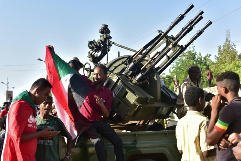 Young Sudanese sit atop a military vehicle as the country's second new military leader in as many days announced on April 13, 2019 the release of prisoners, the lifting of a curfew, and other measures