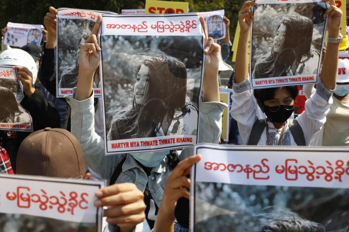 Mandalay University graduates hold posters with an image of Mya Thwet Thwet Khine, a 19-year old woman shot by police on February 9 in Naypyitaw, during an anti-coup protest in Mandalay, Myanmar, February 14, 2021. / Credit: AP