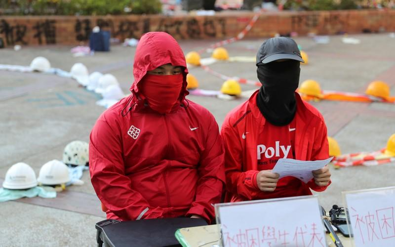 Protesters address the media at the campus of the Polytechnic University in Hong Kong