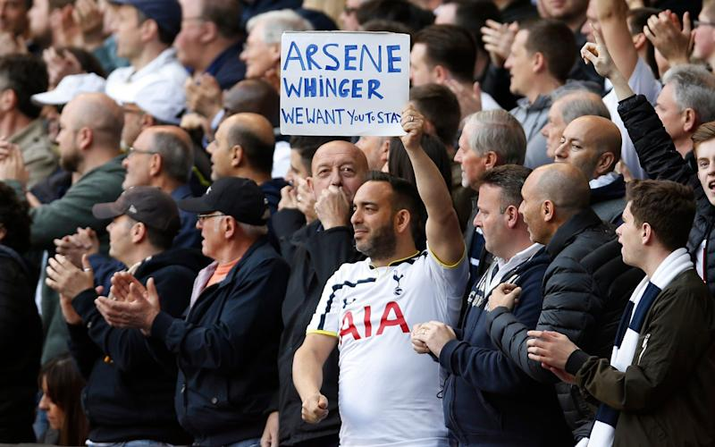 Tottenham fan holds up a banner for Arsenal manager Arsene Wenger - Credit: Paul Childs/REUTERS