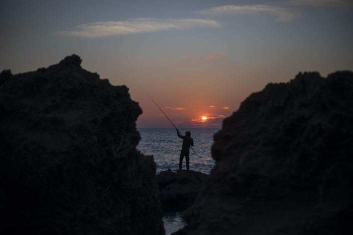 A man collapses his fishing rod as the sun sets over the Mediterranean Sea, in Gador nature reserve near Hadera, Israel, Sunday, Feb. 21, 2021. Israel has closed its Mediterranean beaches following an offshore oil spill that has devastated the country's coastline in what officials are calling one of the country's worst ecological disasters. (AP Photo/Ariel Schalit)