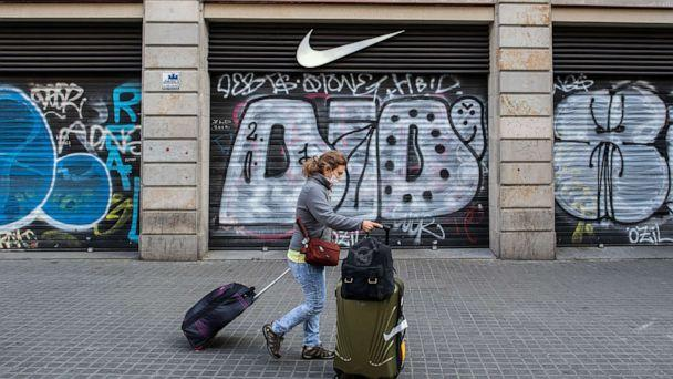 PHOTO: A tourist wears a protective mask as she carries her suitcases past a closed Nike store at Las Ramblas, March 15, 2020, in Barcelona, Spain. (David Ramos/Getty Images)