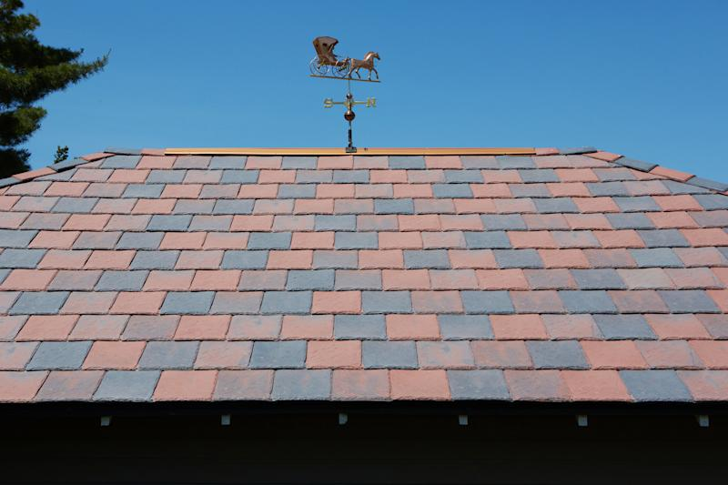 This 2012 photo provided by DaVinci Roofscapes shows a red and grey colored roof that replaced a storm damaged black one at Carol and Ray Knoff's home in Vinton, Iowa. The colors, produced by DaVinci Roofscapes, are typical of the original roofs on Victorian homes. (AP photo/DaVinci Roofscapes)