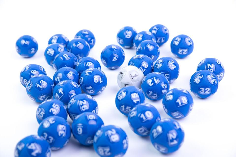 One white Powerball sits amongst a number of blue balls used in lottery draws.