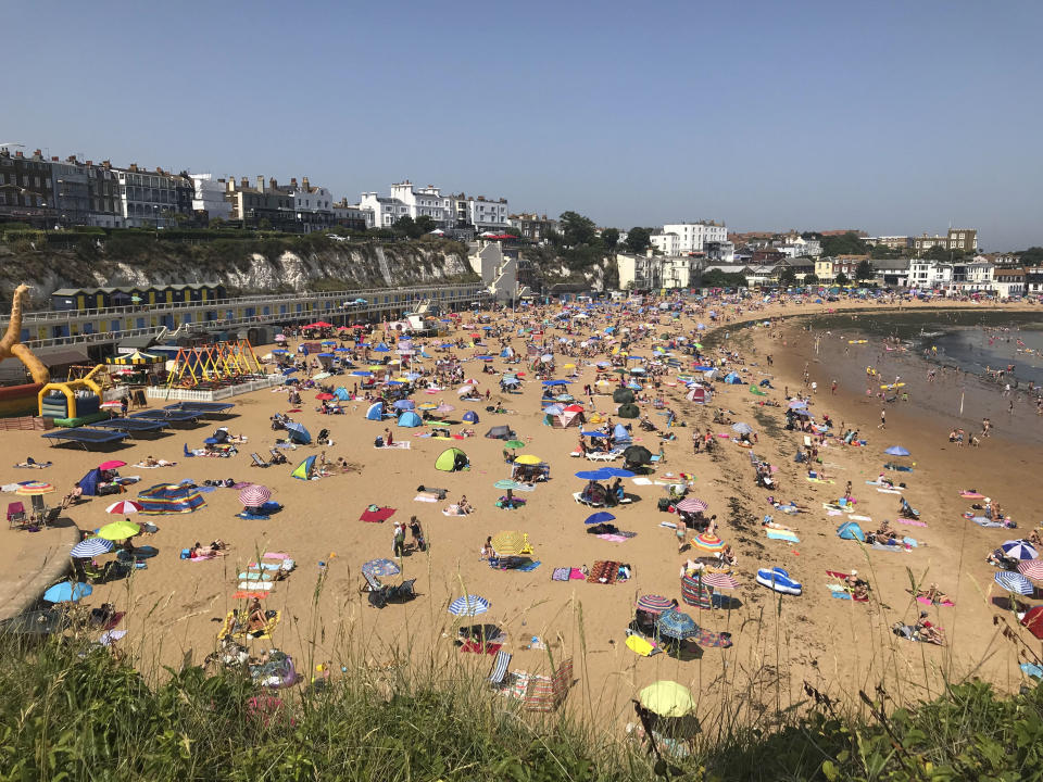 People flock to Broadstairs beach in Kent, England, Thursday July 25, 2019. Paris and London and many parts of Europe are bracing for record temperatures as the second heat wave this summer bakes the continent. The Paris area could be as hot as 42 C (108 F) Thursday as a result of hot, dry air coming from northern Africa that's trapped between cold stormy systems. (Wesley Johnson/PA via AP)