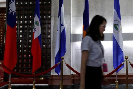 A woman walks past an El Salvador flag (R) inside the Taiwan Ministry of Foreign Affairs in Taipei, Taiwan, August 21, 2018.  REUTERS/Stringer