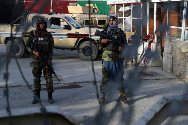 Taliban fighters stand guard at a checkpoint