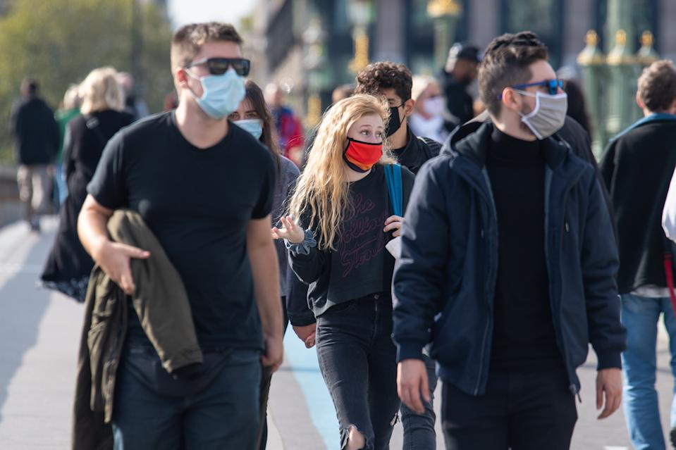 People wearing protective face masks in Westminster, London, after a range of new restrictions to combat the rise in coronavirus cases came into place in England.