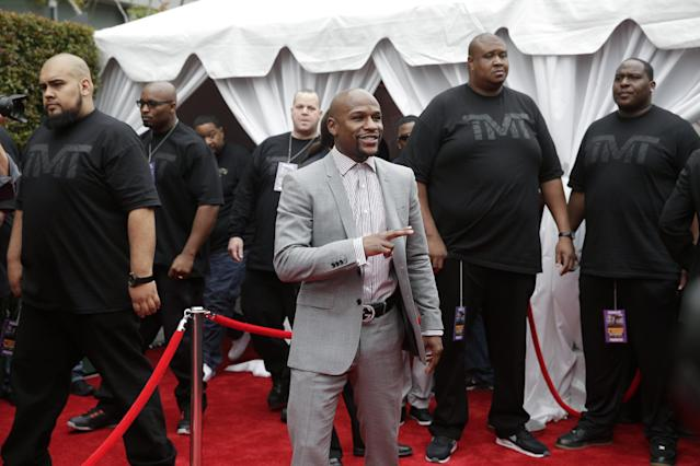Floyd Mayweather Jr., center, arrives for a news conference, Wednesday, March 11, 2015, in Los Angeles. Mayweather is scheduled to fight Manny Pacquiao, of the Philippines, in Las Vegas on May 2. (AP Photo/Jae C. Hong)