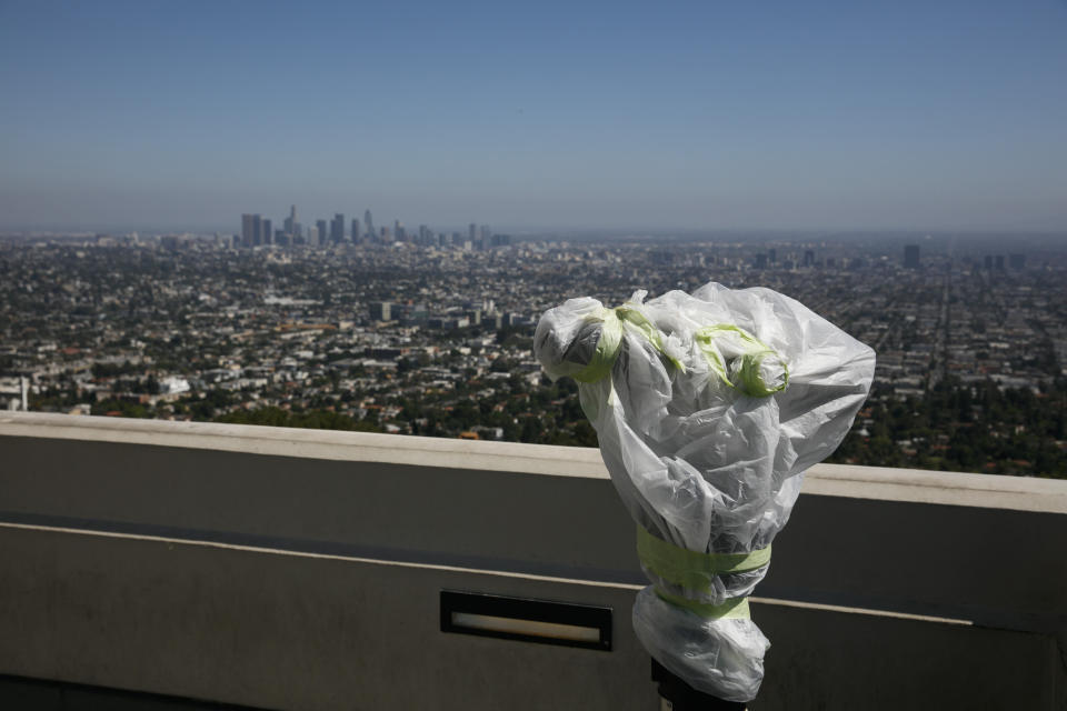 """A telescope is seen wrapped in plastic to prevent the spread of COVID-19 at the Griffith Observatory overlooking downtown Los Angeles, Wednesday, July 15, 2020. Coronavirus cases have surged to record levels in the Los Angeles area, putting the nation's largest county in """"an alarming and dangerous phase"""" that if not reversed could overwhelm intensive care units and usher in more sweeping closures, health officials said Wednesday. (AP Photo/Jae C. Hong)"""
