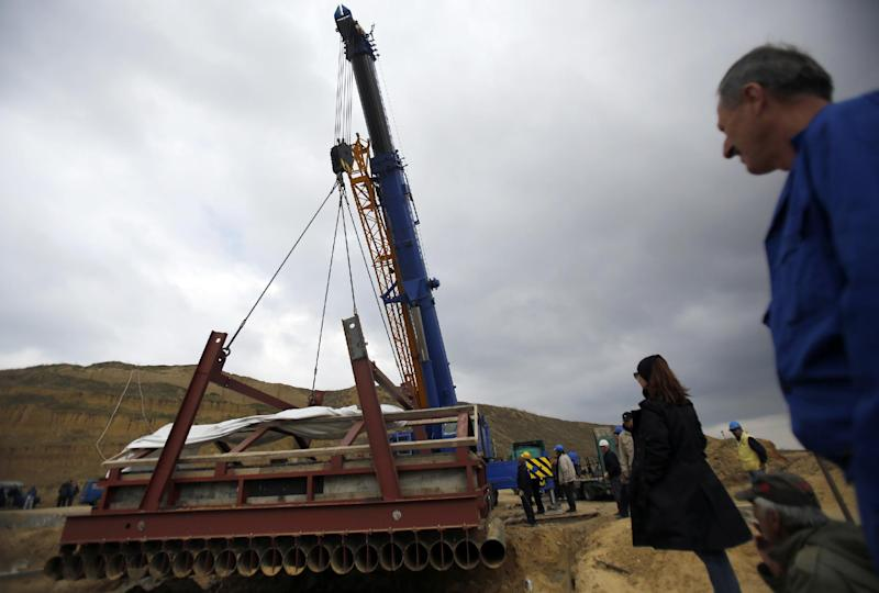A crane lifts the skeleton of a female southern mammoth named Vika at an open pit coal mine in Kostolac, 80 kilometers (50 miles) east of Belgrade, Serbia, Friday, April 11, 2014. Vika, a complete mammoth skeleton, discovered by Serbian archaeologists in 2009 inside the Kostolac open coal pit mine, was moved from the spot where it was found to a secure location because the pit mine threatened to endanger the safety of the remains. (AP Photo/Darko Vojinovic)