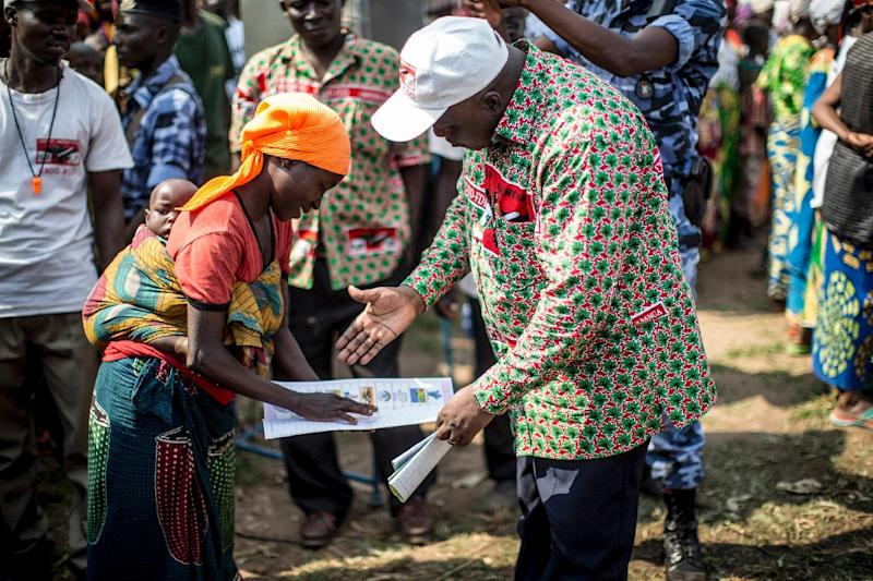 Pascal Nyabenda, president of the National Council for the Defence of Democracy - Forces for the Defence of Democracy party explains how to vote to woman at a rally in Rubiza, Burundi, on June 23, 2015 (AFP Photo/Marco Longari)