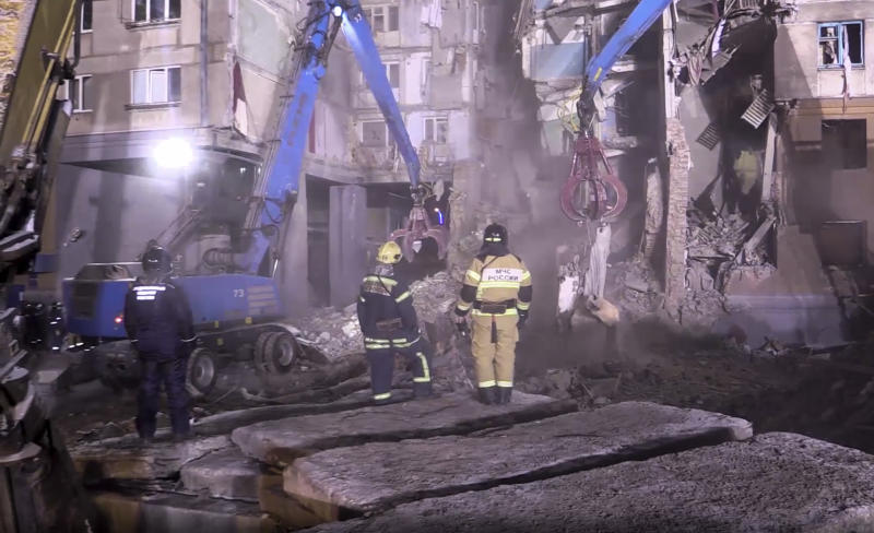 This image made from video and provided by the Russian Emergency Situations Ministry shows Emergency Situations employees working at the scene of a collapsed section of an apartment building, in Magnitigorsk, a city of 400,000 about 1,400 kilometers (870 miles) southeast of Moscow, Russia, Thursday, Jan. 3, 2019. Search crews have pulled more bodies from a huge pile of rubble at a collapsed Russian apartment building. (Russian Ministry for Emergency Situations photo via AP)
