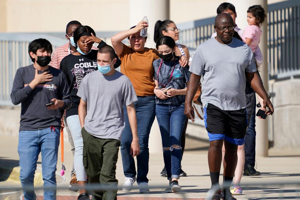 Families depart a performing arts center Wednesday in Mansfield, Texas, after being united with students from Timberview High School. Police in Texas arrested a student suspected of opening fire during a fight at the Arlington-area high school, leaving four people injured.