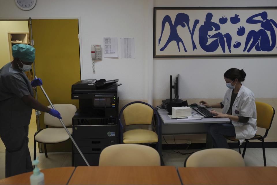 Aurelie Gouel, works on her computer as a medical staff member cleans the floor at Bichat Hospital, AP-HP, in Paris, Wednesday, Dec. 2, 2020. One of the biggest hospitals in Paris, Bichat Hospital, this month reopened all 22 of its operating rooms. It is once again performing surgeries that were stopped during virus surges that pushed France's death toll past 55,000. (AP Photo/Francois Mori)