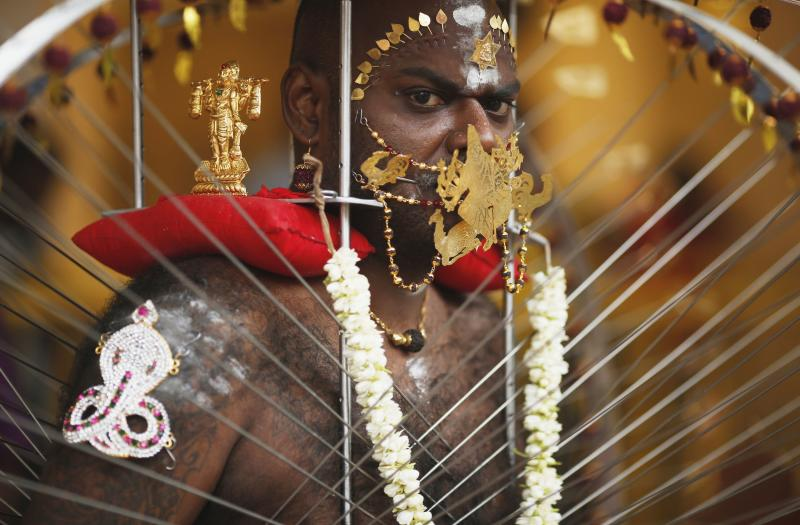 A devotee carrying his kavadi waits to start his procession during Thaipusam festival in Singapore