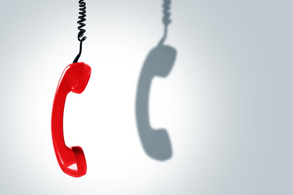 Retro red telephone handset with a dark shadow. Concepts of hotline, support or phone scams.