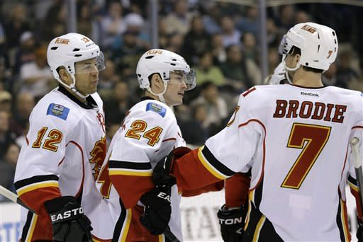 Calgary Flames' Jarome Iginla (12) and T.J. Brodie (7) celebrate with Jiri Hudler (24) of Czech Republic following his goal against the Dallas Stars in the second period of an NHL hockey game Monday, March 18, 2013, in Dallas. (AP Photo/Tony Gutierrez)