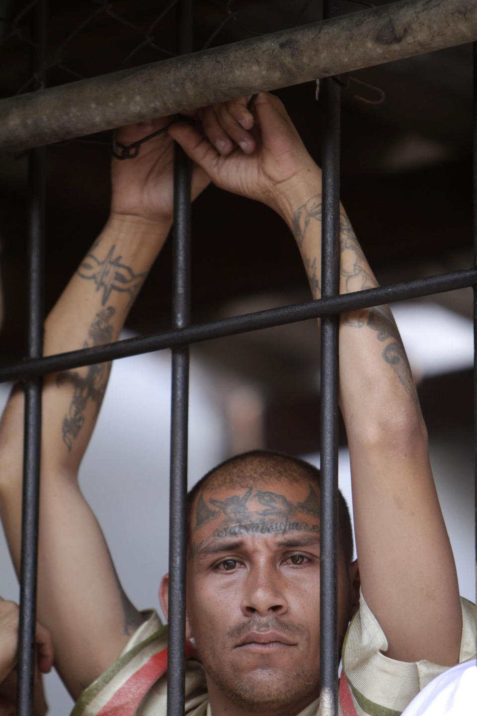 Behind bars, a Mara Salvatrucha gang member attends a mass celebrated by Archbishop Luigi Pezzuto, Apostolic Nuncio to El Salvador, and head army and police chaplain Monsignor Fabio Colindres at a prison in Ciudad Barrios, El Salvador, Monday, March 26, 2012. According to Dionisio Aristides Umanzor, known as El Sirra, leader of the Mara Salvatrucha gang, leaders of the Mara Salvatrucha and the Mara 18, El Salvador's two largest street gangs, have reached a truce, reducing the country's homicide rate, one of the highest in the world. (AP Photo/Luis Romero)