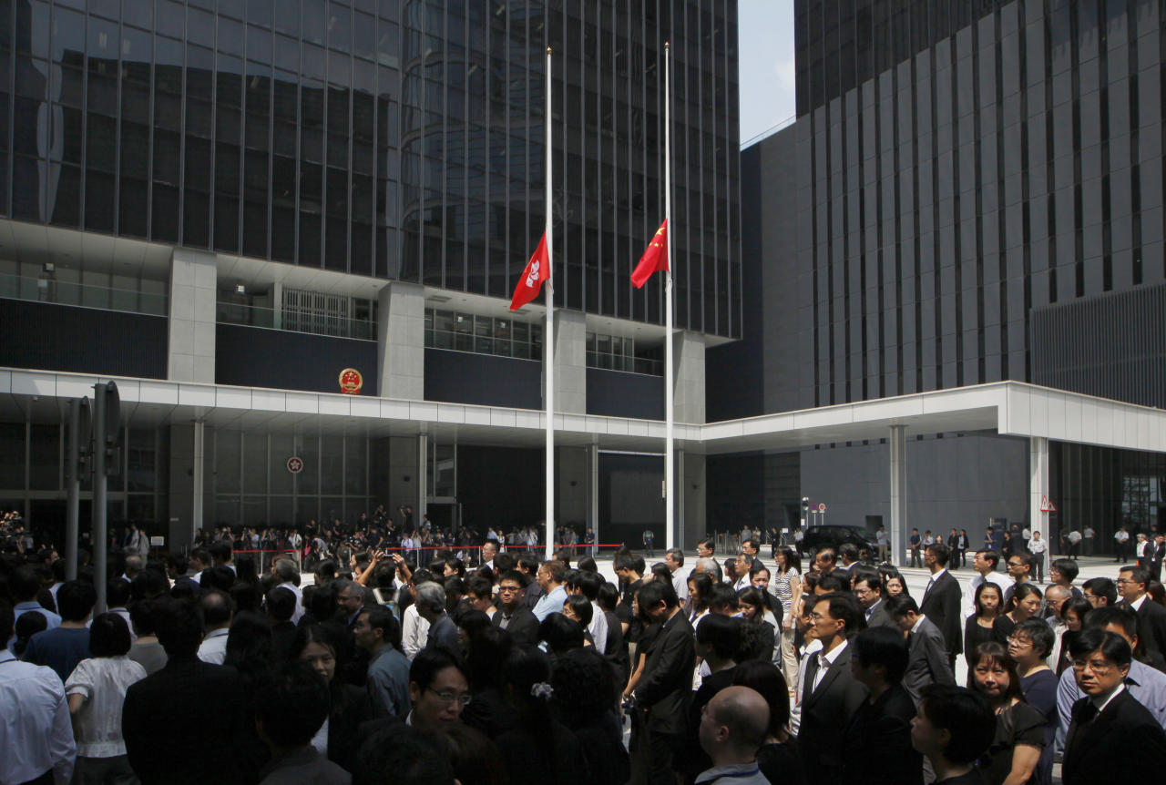 Hong Kong government officials pay tribute to victims who were killed in a ferry collision, with flying Chinese and Hong Kong flags at half-mast in the Central Government Office in Hong Kong Thursday, Oct. 4, 2012. Shock over Monday's crash, which left 38 dead, gave way to outrage Wednesday over what experts concluded was human error. (AP Photo/Kin Cheung)