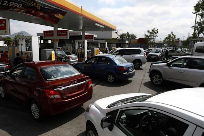 Cars stand in line at a gasoline station as they wait to fuel up after a protest against the increase in subway ticket prices in Santiago