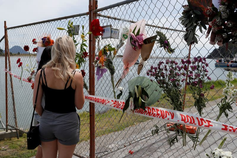 FILE PHOTO: A man looks at a memorial at the harbour in Whakatane, following the White Island volcano eruption in New Zealand