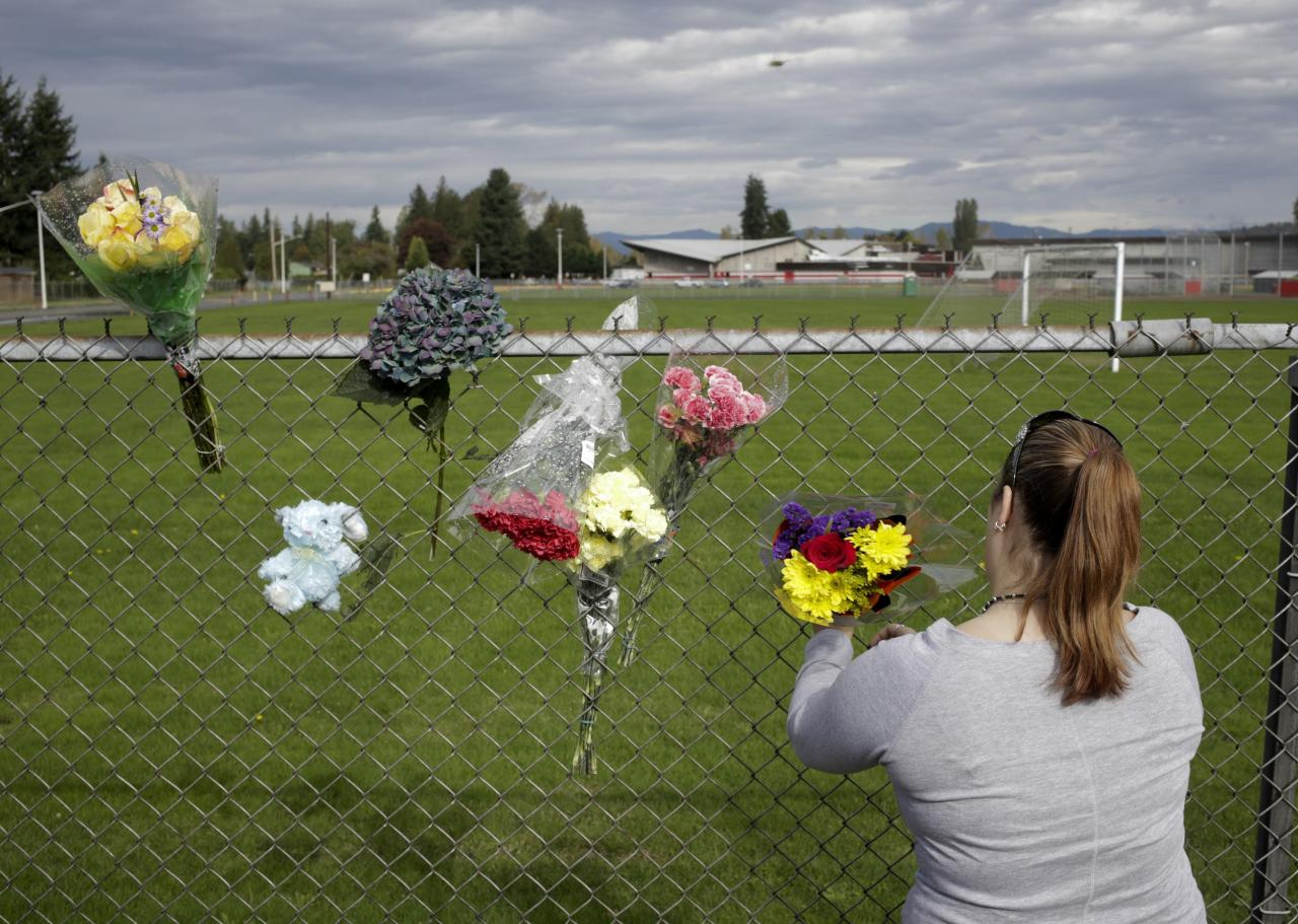 Visitors leave flowers the day after a shooting at Marysville-Pilchuck High School in Marysville, Washington October 25, 2014. A student fatally shot one classmate and wounded four others when he opened fire in the cafeteria of his Washington state high school on Friday, following a fight with fellow students, authorities said. The shooter took his own life as Marysville-Pilchuck High School students scrambled to safety in the latest outburst of deadly violence at an American school. REUTERS/Jason Redmond (UNITED STATES - Tags: CRIME LAW EDUCATION)