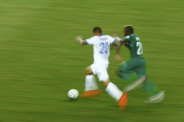 Greece's Holebas and Ivory Coast's Serey Die run for the ball during their 2014 World Cup Group C soccer match in Fortaleza