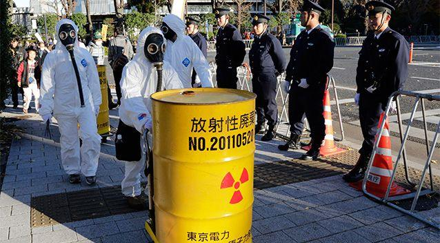 Anti-nuclear protesters wearing protective suits carry a mock nuclear waste during a march as policemen stand guard near the Diet building in Tokyo. Photo: AP.