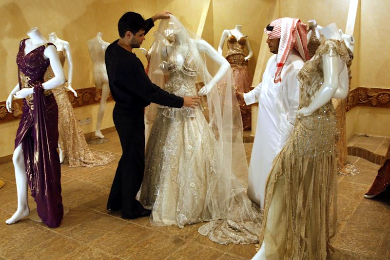 FILE - In this Sunday, Aug. 3, 2008 file photo, a Saudi man, right, buys a wedding dress at a shop in Riyadh, Saudi Arabia. With global attention focused on upheaval elsewhere in the Middle East, Saudi Arabia quietly intensified its clampdown on dissent in 2013, silencing democracy advocates and human rights defenders with arrests, trials and intimidation in what reformists say was one of the darkest years ever for their efforts in the powerful U.S.-allied Gulf state. (AP Photo, File)