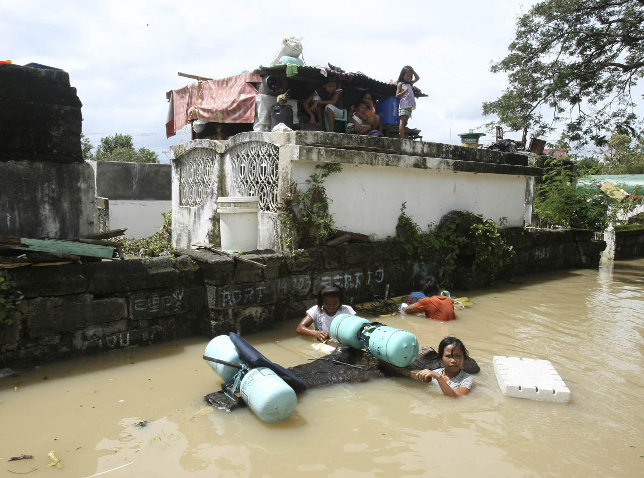 Residents seek temporary shelter on tombs at a cemetery at Calumpit township, Bulacan province, north of Manila, Philippines Monday Oct. 3, 2011. Floodwaters slowly receded Monday in many parts of the northern Philippines after two typhoons that killed nearly 60 people, amid appeals for more boats to bring food and water to residents refusing to abandon inundated homes. (AP Photo/Bullit Marquez)