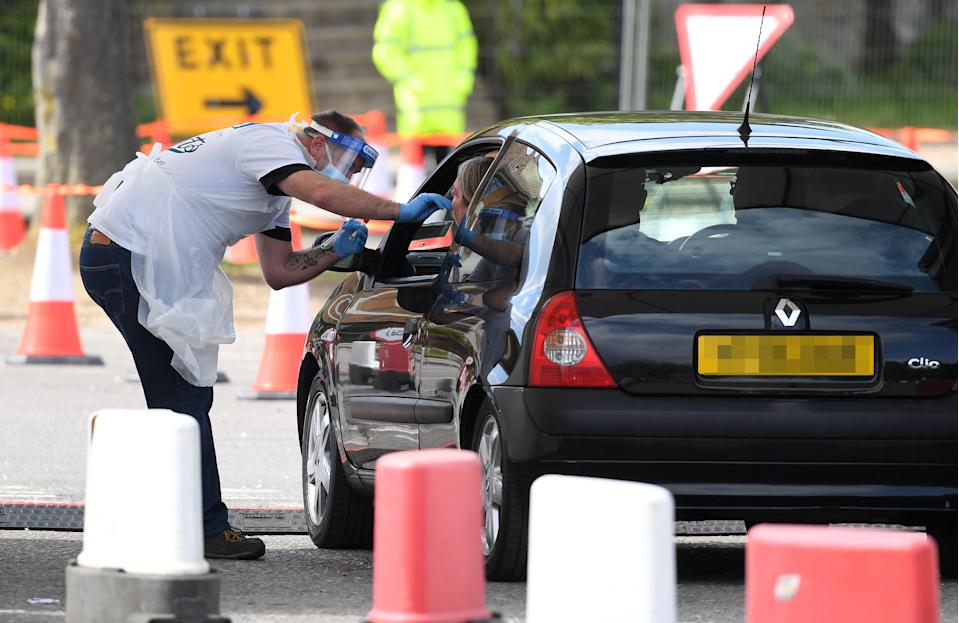 Numberplate pixelated by PA picture desk. A medical worker takes a swab at a drive-in coronavirus testing facility at the Chessington World of Adventures Resort in south west London, as the UK continues in lockdown to help curb the spread of the coronavirus.