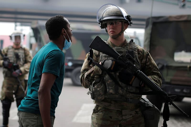 A man confronts a National Guard member as they guard the area in the aftermath of a protest in Minneapolis