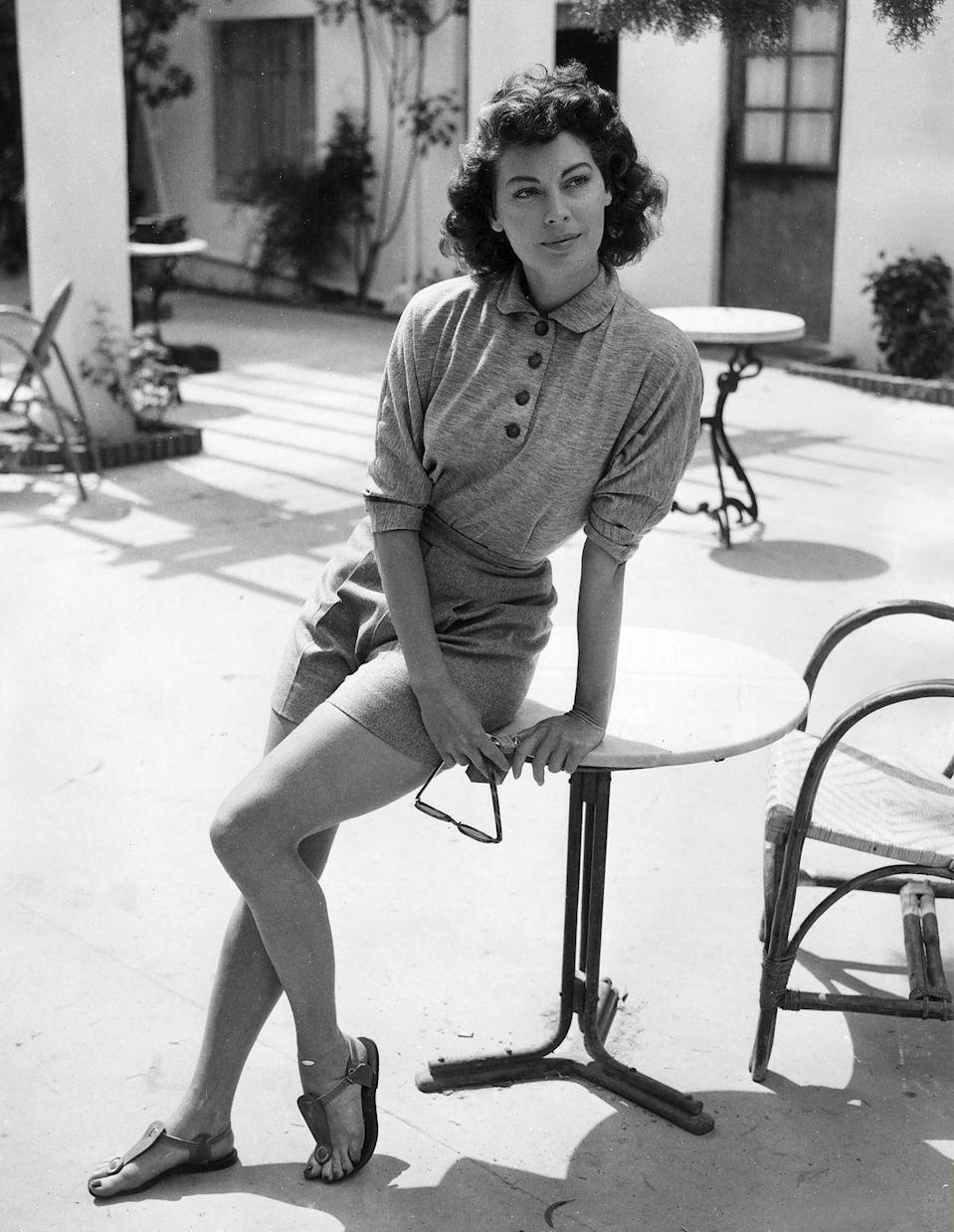 <p>At ease, Gardner strikes a casual pose in a knit top, pressed shorts, and flat summer sandals. The actress bought a stucco cottage set on a cliff in Nichols Canyon, which she decorated as a sunny escape for herself between marriages. </p>
