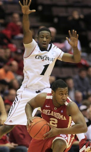 Oklahoma guard Steven Pledger (2) is defended by Cincinnati guard Cashmere Wright (1) in the first half of an NCAA college basketball game, Thursday, Dec. 29, 2011, in Cincinnati. (AP Photo/Al Behrman)