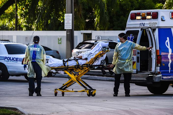 Medics transfer a patient on a stretcher from an ambulance outside of Emergency at Coral Gables Hospital where Coronavirus patients are treated in Coral Gables near Miami, on July 30, 2020.(Chandan Khanna/AFP via Getty Images)