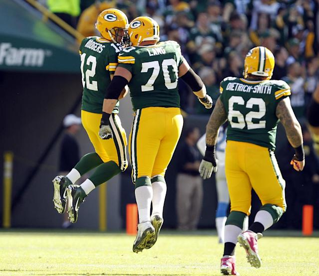 Green Bay Packers quarterback Aaron Rodgers celebrates with teammate T.J. Lang (70) after Rodgers threw an 83-yard touchdown pass to James Jones during the second half of an NFL football game against the Detroit Lions Sunday, Oct. 6, 2013, in Green Bay, Wis. (AP Photo/Mike Roemer)