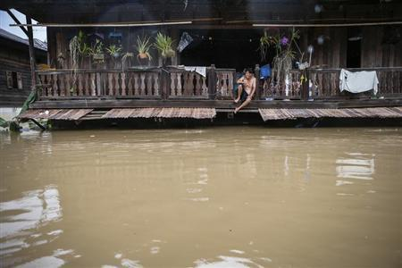 A man sits on the second floor of his house, affected by floodwaters, at Kabin Buri district in Prachin Buri September 29, 2013. REUTERS/Athit Perawongmetha