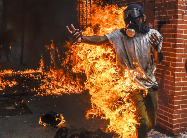 <p>A demonstrator catches fire, after the gas tank of a police motorbike exploded, during clashes in a protest against Venezuelan President Nicolas Maduro, in Caracas on May 3, 2017. (Photo: Juan Barreto/AFP/Getty Images) </p>