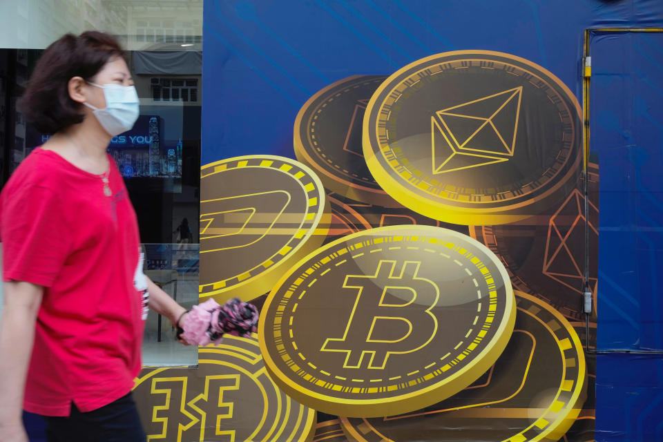 FILE - In this June 1, 2021, file photo, a woman walks past an advertisement for the Bitcoin cryptocurrency in Hong Kong. China's biggest banks promised Monday, June 21, 2021, to refuse to help customers trade Bitcoin and other cryptocurrencies after the central bank said executives were told to step up enforcement of a government ban. (AP Photo/Vincent Yu, File)