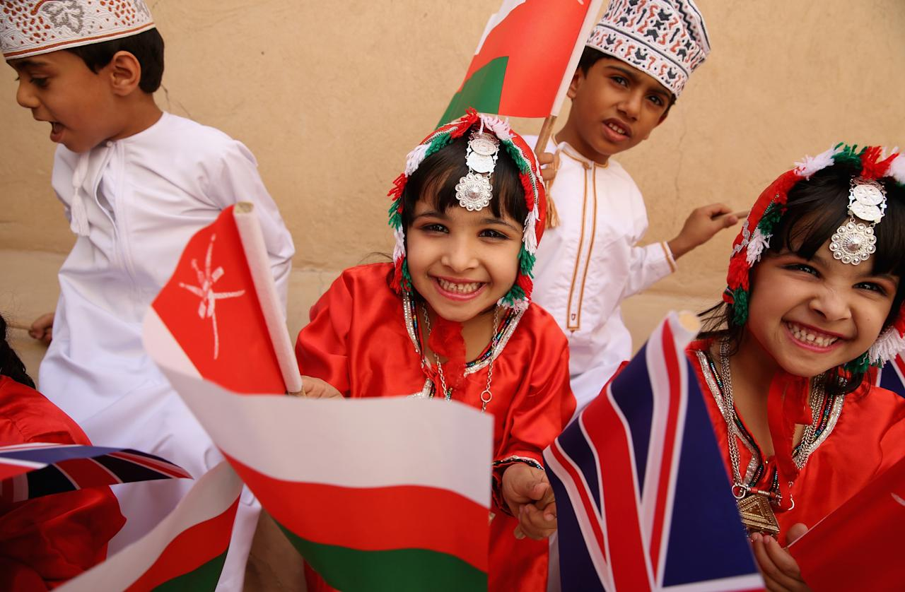 NIZWA, OMAN - MARCH 18:  Young children wave flags as Prince Charles, Prince of Wales and Camilla, Duchess of Cornwall visit Nizwa Fort on the eighth day of a tour of the Middle East on March 18, 2013 in Nizwa, Oman. The Royal couple are on the fourth and final leg of a tour of the Middle East taking in Jordan, Qatar, Saudia Arabia and Oman.  (Photo by Chris Jackson/Getty Images)