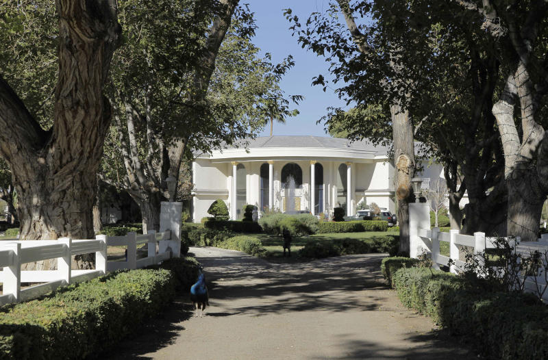 """<p> FILE - In this Friday, Nov. 12, 2010, file photo Wayne Newton's home is framed at the end of a tree-lined lane on a 52-acre estate in Las Vegas. Newton is moving out of this sprawling estate of 45 years. The crooner's family members and a spokesman confirmed Wednesday June 5, 2013, that the downsizing to another mansion involving Newton, family members and a menagerie of exotic animals is taking place this week. Property records show the move is to a $3 million mansion about a mile from Newton's beloved """"Casa de Shenandoah.""""(AP Photo/Julie Jacobson, file)"""