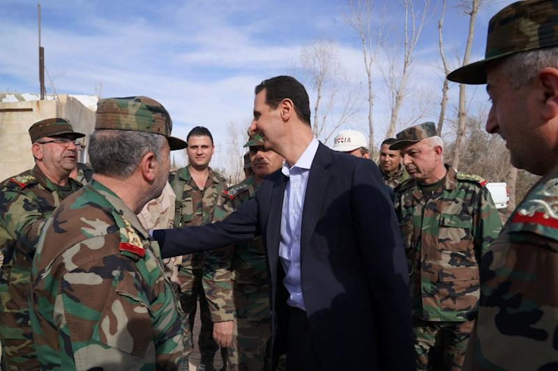 Syrian President Bashar al-Assad greets troops in the Eastern Ghouta district outside Damascus on March 18, 2018, in his first visit after its recapture from rebels in a Russian-backed offensive (AFP Photo/HO)