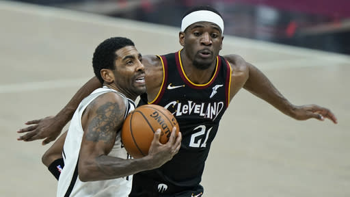 Brooklyn Nets' Kyrie Irving, front, drives to the basket against Cleveland Cavaliers' Damyean Dotson during the second half of an NBA basketball game, Wednesday, Jan. 20, 2021, in Cleveland. The Cavaliers won 147-135 in double-overtime. (AP Photo/Tony Dejak)