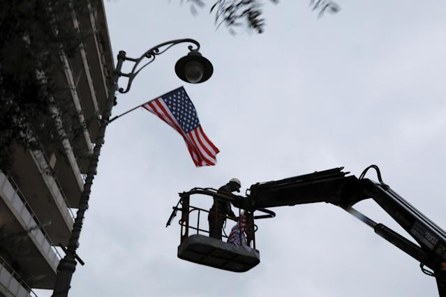 <p>A laborer hangs a U.S. national flag on a lamp post along a street where the U.S. consulate in located in Jerusalem, Dec. 6, 2017. (Photo: Ammar Awad/Reuters) </p>