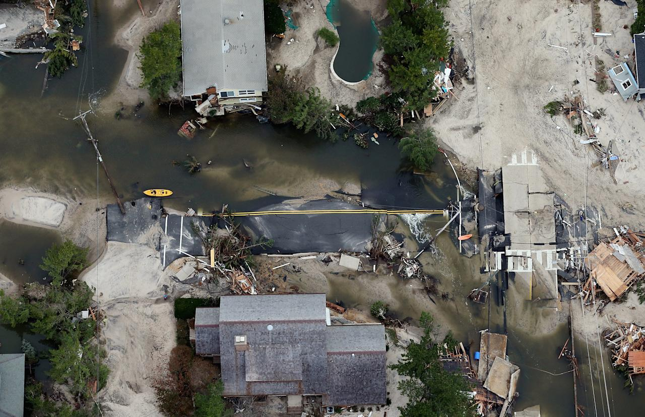 The remains of a road are mired in debris and water from Superstorm Sandy on October 31, 2012 in Mantoloking, New Jersey. At least 50 people were reportedly killed in the U.S. by Sandy with New Jersey suffering massive damage and power outages.  (Photo by Mario Tama/Getty Images)