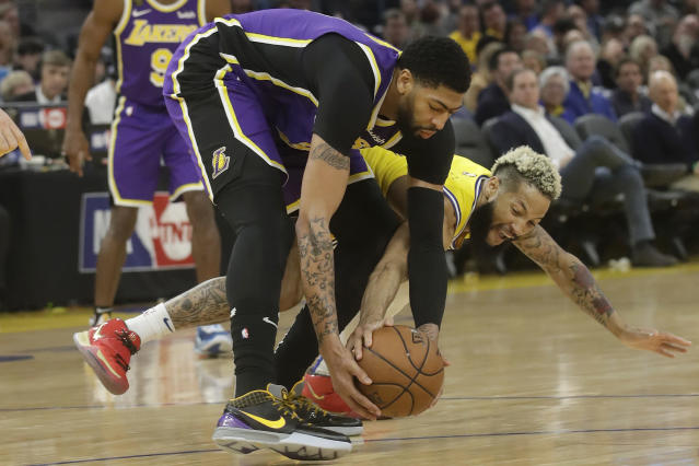 Golden State Warriors guard Ky Bowman, bottom, reaches for the ball under Los Angeles Lakers forward Anthony Davis during the first half of an NBA basketball game in San Francisco, Thursday, Feb. 27, 2020. (AP Photo/Jeff Chiu)