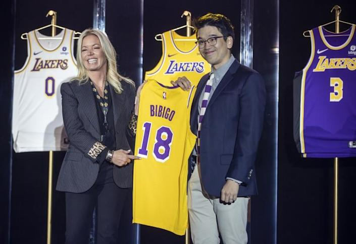 EL SEGUNDO, CA - September 20: Jeanie Buss, CEO / Governor / Co-owner of the Los Angeles Lakers, left, and Sun-Ho Lee, Bibigo Head of Global Business Planning, hold a jersey featuring the Bibigo logo, as the Lakers host a 2021-2022 season kick-off event to unveil and announce a new global marketing partnership with Bibigo, which will appear on the Lakers' jersey at the UCLA Health Training Center in El Segundo on Monday, Sept. 20, 2021. (Allen J. Schaben / Los Angeles Times)