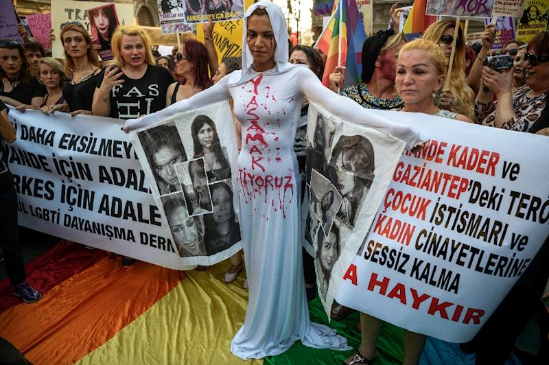 "A LGBT member stands in front of a banner with make up on her face and a writing on her body ""I want to live"" on August 21, 2016 in Istanbul during a demonstration for the murdering of a transgender activist Hande Kader (AFP Photo/Ozan Kose)"